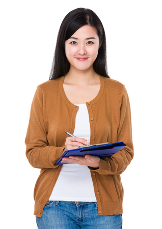 Asian woman take note on clipboard Stock Photo