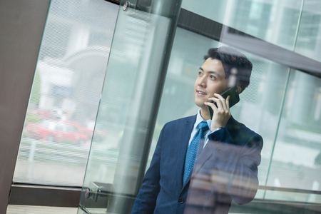 Businessman talk to mobile phone inside office building 免版税图像