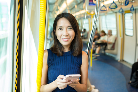 compartment: Woman using mobile phone in metro compartment Stock Photo