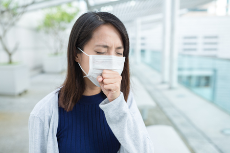 Woman feeling sick and wearing face mask Standard-Bild