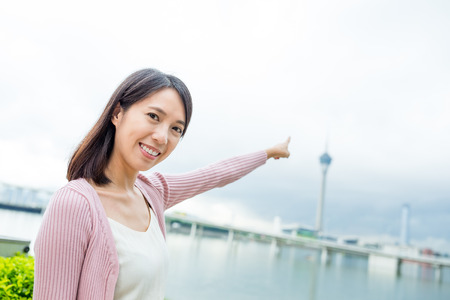 Woman finger pointing the Macao tower