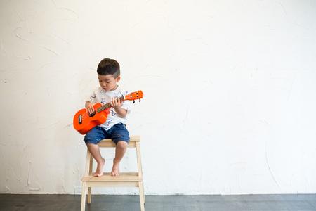 Little boy play with ukulele