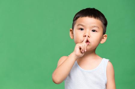 静けさのジェスチャーを作る少年