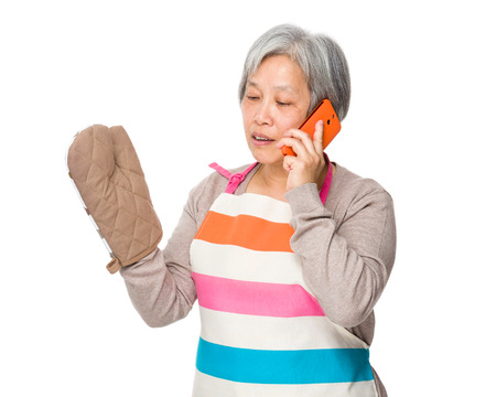 japanese cookery: Asian old housewife talk to cellphone with oven glove