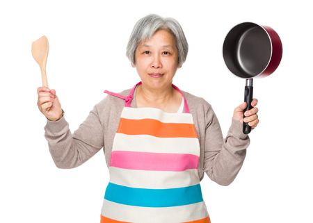 Old woman hold up with cooking tool photo