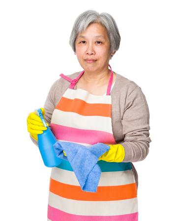 Old woman use of the bootle spray and rag photo