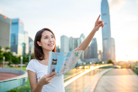 far away: Woman using city map and finger pointing far away Stock Photo