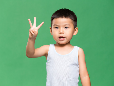 Little boy showing three finger Standard-Bild