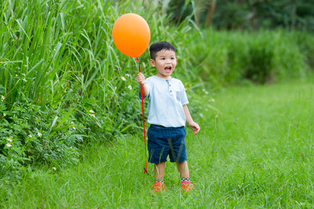 chasing: Thrilled little boy holding a flying ballon