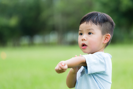 itchy: Young boy feeling itchy and scratching his arm Stock Photo