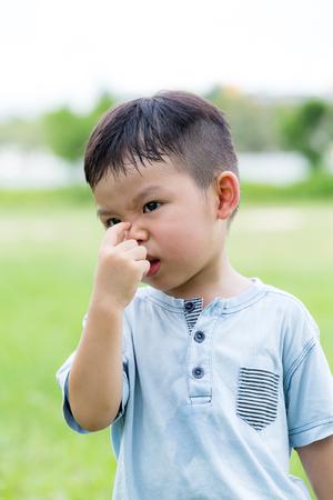 Little boy pinch his nose