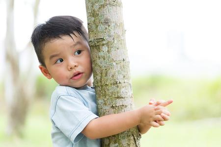Little boy climb up on the tree