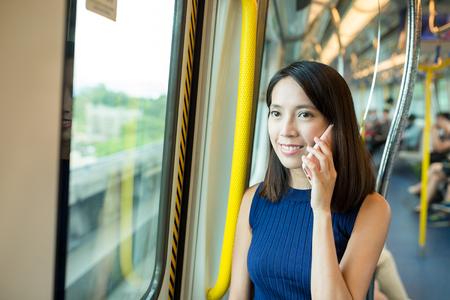 make public: Woman talk to mobile phone in train Stock Photo