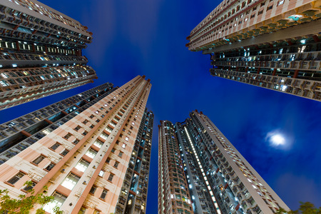 overpopulated: Apartment building from low angle at night Stock Photo