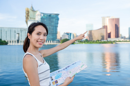 far away look: Woman using paper map and finger pointing far away
