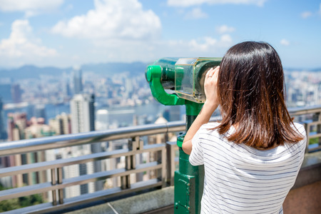 shortsighted: Woman looking though the binocular in the Peak of Hong Kong Stock Photo