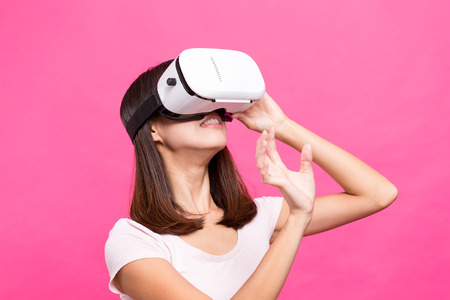 though: Young Woman playing with VR device
