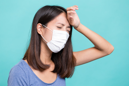 transmissible: Woman wearing face mask and suffer from headache Stock Photo