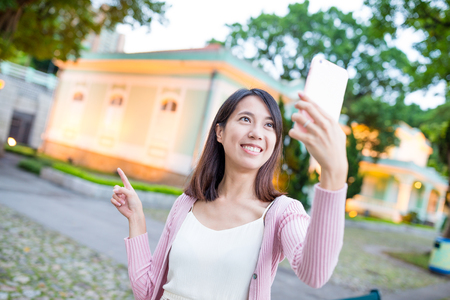 take a history: Woman taking selfie by mobile phone in Taipa of Macau city Stock Photo