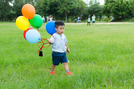 Small kid hold with group of balloon Stock Photo
