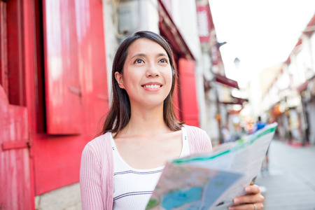 far away look: Woman holding a paper map in Macau city