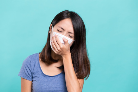 transmissible: Woman wearing face mask and cough Stock Photo
