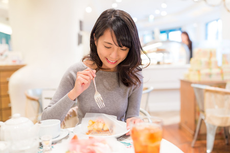 Woman having cake in dessert shop
