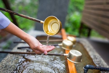 Woman washes her hand in fountain of Japanese temple Stock Photo
