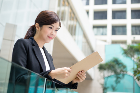 Asian business woman reading on clipboard