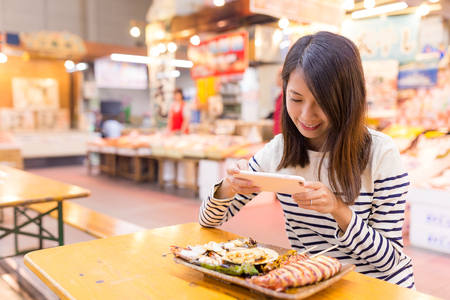 Woman taking photo before having her assorted seafood Stock Photo
