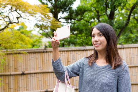 Woman taking photo by cellphone at Japanese old town