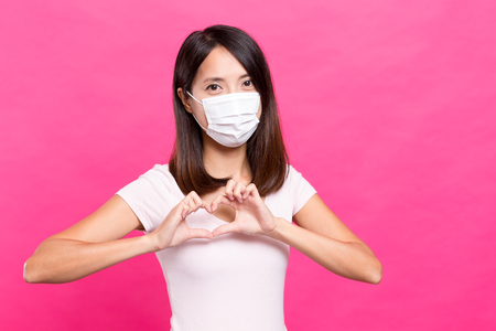 transmissible: Woman with mask show a heart sign