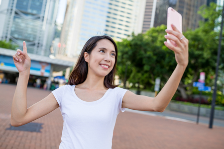 Woman taking photo by mobile phone in Hong Kong city
