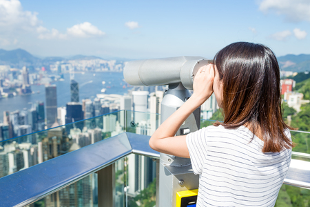shortsighted: Woman looking though the telescope in the Peak Stock Photo