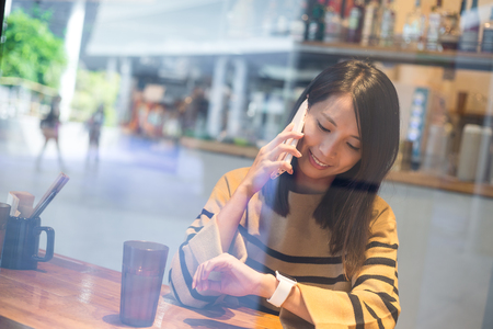 japanese people: Woman talk to mobile phone and look at smart watch Stock Photo