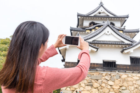 take a history: Woman taking photo on Hikone castle