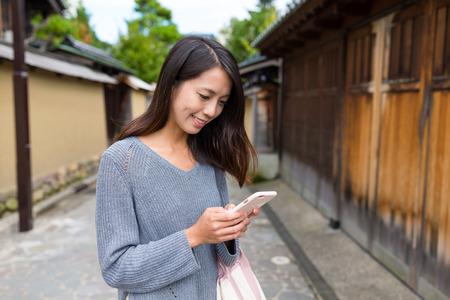 Woman looking at cellphone at kanazawa city
