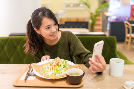 Woman taking selfie by cellphone in restaurant Stock Photo