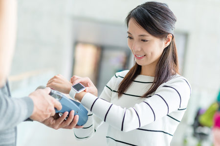 Woman using smart watch to pay on pos terminal