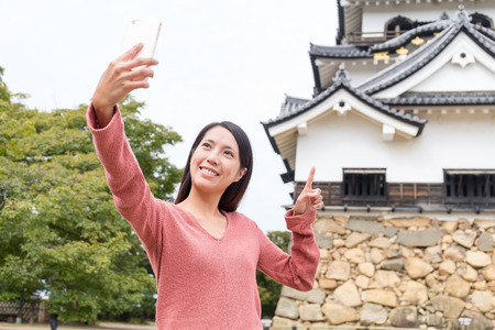 Woman taking selfie by mobile phone at Hikone castle