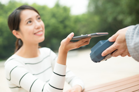 Woma paying on pos terminal by cellphone Stock Photo