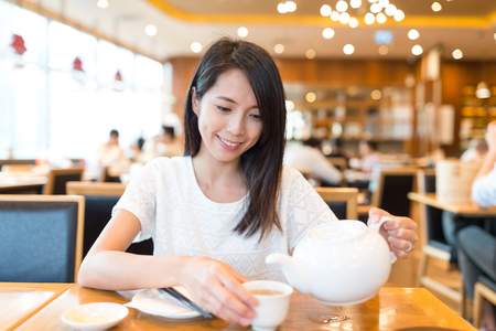 Woman drinking tea in chinese restaurant