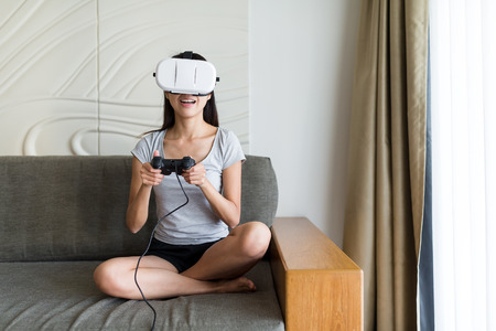 Woman play with virtual reality device at home Stock Photo