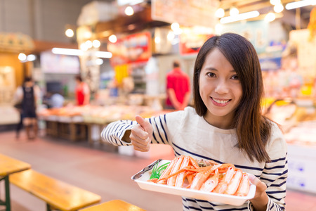 Woman holding snow crab and showing thumb up