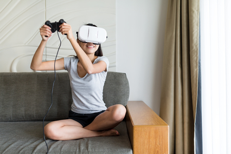 Woman play game with virtual reality device and joystick in living room Stock Photo
