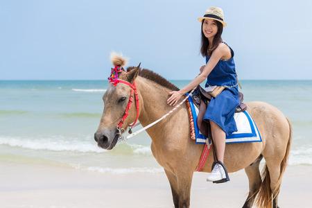 砂浜で馬に乗って若い女性