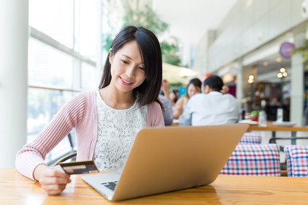 Woman using laptop computer to pay the bill online Stock Photo