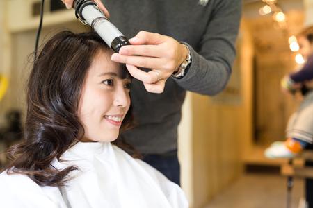 Vrouw die haar haar in salon maakt Stockfoto