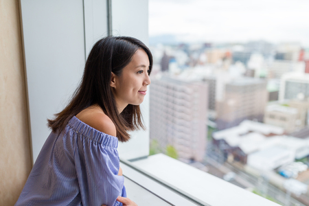 Woman looking though the view of city inside lookout Stock Photo