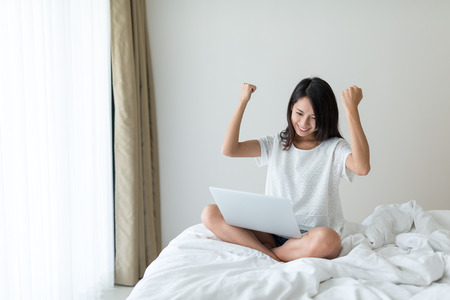 Excited Woman use of laptop computer Standard-Bild